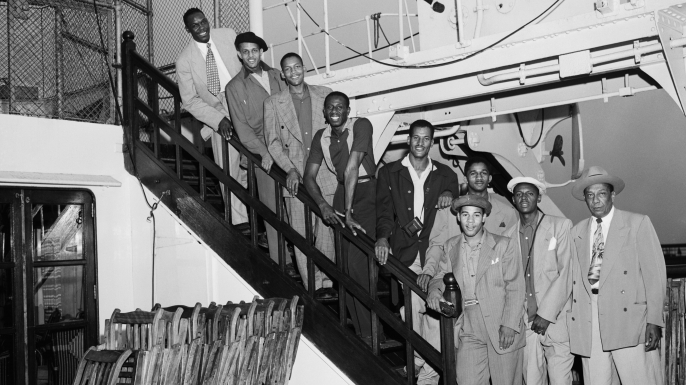 "Members of the Globetrotters basketball team are shown arriving in New York aboard the liner Mauretania. From top to bottom are: Louis Pressly; William ""Rookie"" Brown; Boyd Buie; Reece ""Goose"" Tatum; Frank Washington; Markus Haynes; Sammy Quee; Clarence Wilson; and (in front) manager Winfield Welch. (Credit: Bettmann / Contributor)"