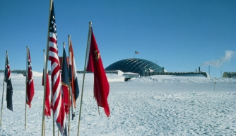 US Amundsen-Scott base at South Pole with flags of Antarctic Treaty Nations visible in foreground. (Credit: DR. DAVID MILLAR/Getty Images)