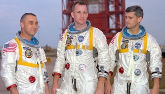 Grissom, White, and Chaffee in front of the launch pad containing their Apollo 1 space vehicle.