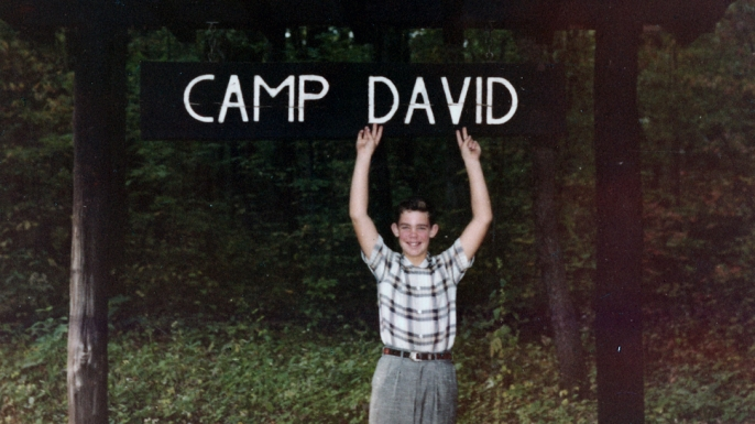 David Eisenhower, grandson of President Dwight D. Eisenhower, poses with Camp David sign, October 1960. (Credit: National Archives)