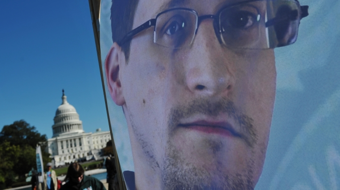 An image of Edward Snowden on the back of a banner during a protest against government surveillance on October 26, 2013. (Credit: MANDEL NGAN/AFP/Getty Images)