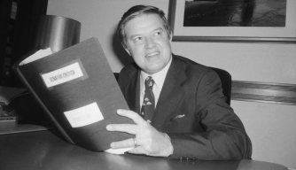 Senator Frank Church (D-Idaho), holds a copy of the Church report, 1976. (Credit: Bettmann/Getty Images)