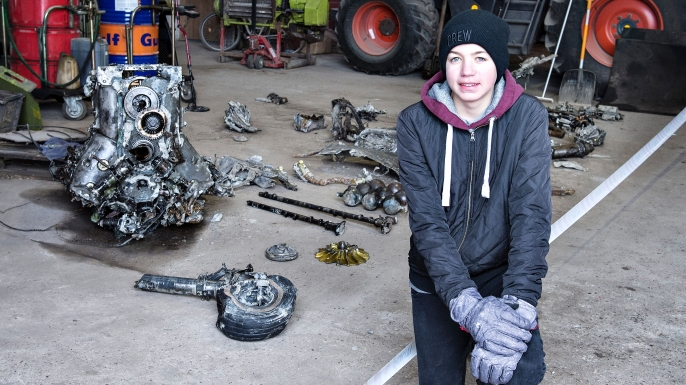 14-year-old Daniel Kristensen on March 7, 2017 in front of debris from the wreck of a World War II aircraft, which Daniel and his father Klaus Kristensen found near Birkelse, in Northern Jutland. (Credit: HENNING BAGGER/AFP/Getty Images)