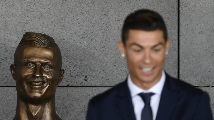 Portuguese footballer Cristiano Ronaldo stands beside a bust presented during a ceremony to rename Madeira's airport in Funchal. (Credit: FRANCISCO LEONG/AFP/Getty Images)