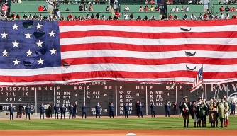 The giant American flag is unfurled as part of pre-game festivities on Patriots' Day. (Credit: Jim Davis/The Boston Globe/Getty Images)
