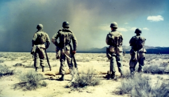 Four men from the 82nd Airborne Division looking at the base of the mushroom cloud of atomic bomb test on April 22, 1952.