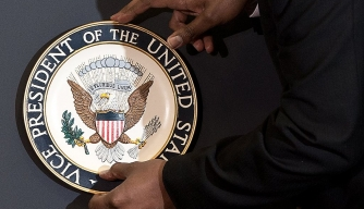 An aide places the vice president's seal on the lectern.