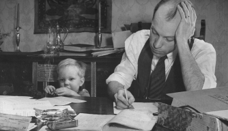 A man working on his 1940 tax returns while his son sits near him playing with toys.