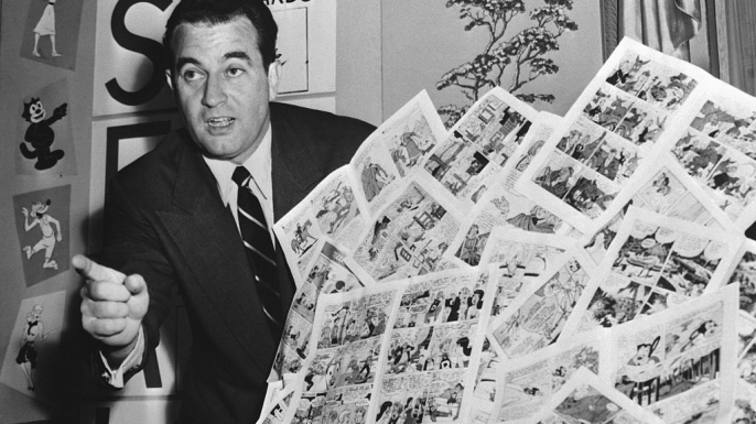 "Charles F. Murphy, Code Administrator of the Comics Magazine Association of America, holding a group of ""approved"" comic books in 1954."