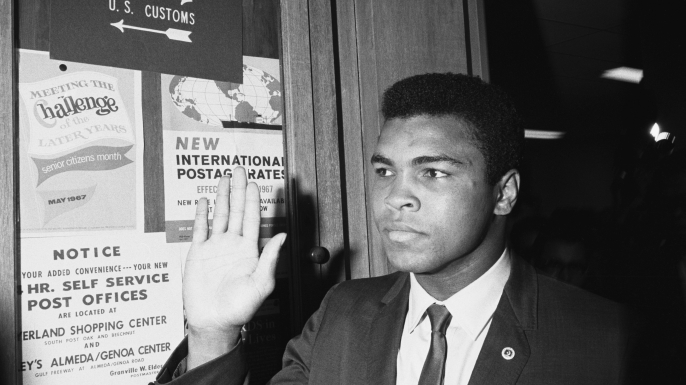 Ali waves at fans as he arrives at the Army Induction Center.