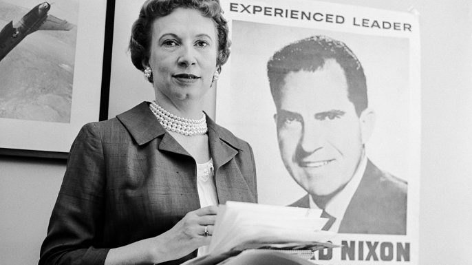 Rose Mary Woods stands in front of a poster for her boss during the 1960 presidential election.