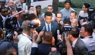 Muhammad Ali talks with the press on his way into court to face trial because of his refusal to be drafted, June 1967.