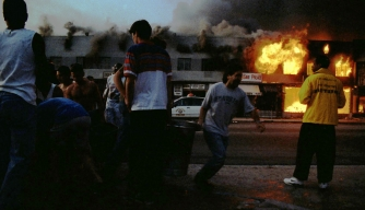 LOS ANGELES - April 30 - Rodney King Riot. Near intersection of Pico Boulevard and Hayworth Avenue, neighborhood residents filling buckets from open hydrant attempting to put out fires burning local businesses as the second night nears of riots that broke out after the policemen who beat Rodney King were found Not Guilty. April 30, 1992