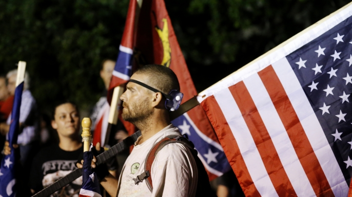 A demonstrator who supports keeping Confederate era monuments joins other protestors before the Jefferson Davis statue was taken down in New Orleans, Thursday, May 11, 2017. (AP Photo/Gerald Herbert)