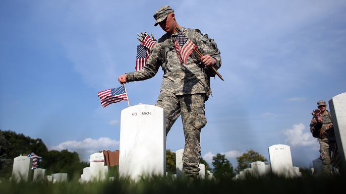 Members of the 3rd U.S. Infantry Regiment place American flags at the graves of U.S. soldiers buried in Section 60 at Arlington National Cemetery in preparation for Memorial Day May 24, 2012. (Credit: Win McNamee/Getty Images)