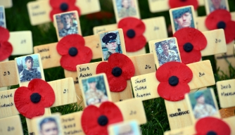 Wooden crosses bearing pictures of fallen servicemen and women and poppy flowers are planted in a memorial field at Saltwell Park in Gateshead, north-east England, on October 29, 2012 ahead of Remembrance Day (Armistice Day) on November 11. AFP PHOTO/PAUL ELLIS