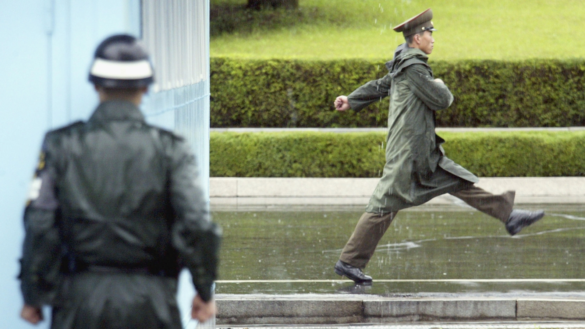 A South Korean soldier (L) looks at a North Korean soldier as he marches past at the truce village of Panmunjom in the demilitarized zone (DMZ) between South and North Korea. (Credit: Chung Sung-Jun/Getty Images)