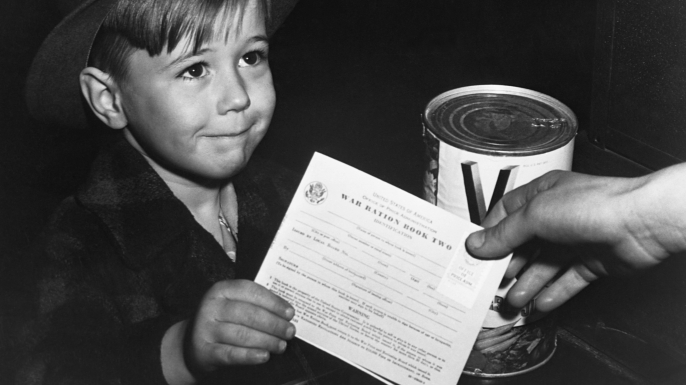 An eager school boy gets his first experience in using War Ration Book Two. With many parents engaged in war work, children are being taught the facts of point rationing for helping out in family marketing. February 1943. (Photo by © CORBIS/Corbis via Getty Images)