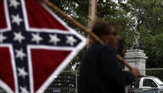 A protester holds a Confederate flag across the street from the Jefferson Davis monument on May 4, 2017.