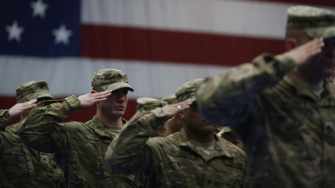 Soldiers from the U.S. Army's 3rd Brigade Combat Team, 1st Infantry Division, salute during the playing of the Star Spangled Banner during a homecoming ceremony in 2014.