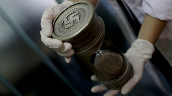 A member of the federal police holds an hourglass with Nazi markings at the Interpol headquarters in Buenos Aires, Argentina. (Credit: Natacha Pisarenko/ AP Photo)