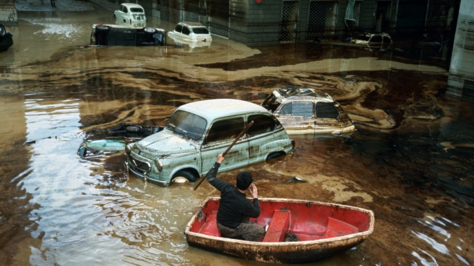 A man paddles a small boat among wrecked cars on a waterlogged street in Florence, following the devastating flood of November 1966, during which the water of the Arno rose as high as 20 feet, submerging sculpture, paintings, mosaics and manuscripts in the city's libraries. (Credit: Vittoriano Rastelli/Corbis via Getty Images)