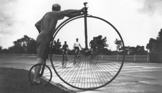 A view through the wheel of a penny-farthing of others racing around a track, 1932. (Credit: Hulton Archive/Getty Images)