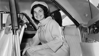 First Lady Jacqueline Kennedy sits in the back seat of a car.  She is wearing a pillbox hat, a wool coat and gloves.  (Credit: Morgan Collection/Getty Images)