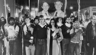 crowd of 12,000 carried flickering candles as they marched to honor Mayor George Moscone and Harvey Milk, (shown in portrait), on November 27, 1979. In foreground is Moscone's daughter, Jennifer, as she leads parade with Cleve Cleveland, Harvey Milk's former assistant. (