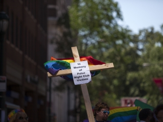 A cross with a sign in memory of the victims of the Pulse nightclub shooting carried during the 2016 Gay Pride Parade on June 12, 2016 in Philadelphia. (Credit: Jessica Kourkounis/Getty Images)