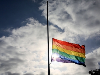 A pride flag stands a half mast during a memorial service in San Diego, California on June 12, 2016, for the victims of the Orlando Nightclub shooting. (Credit: SANDY HUFFAKER/AFP/Getty Images)