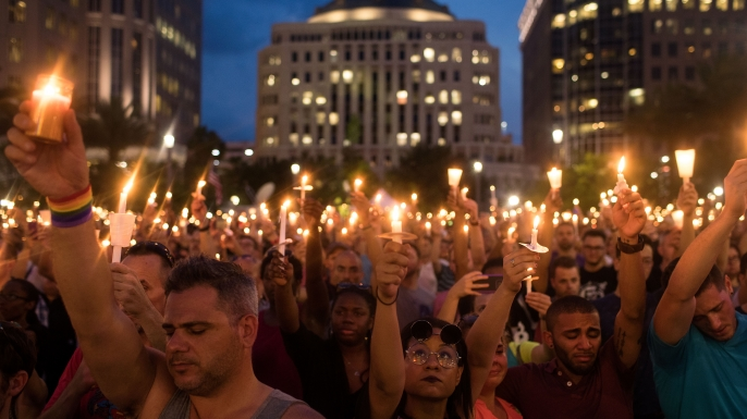 People hold candles during an evening memorial service for the victims of the Pulse Nightclub shootings. (Credit: Drew Angerer/Getty Images)