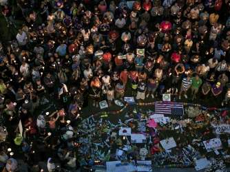 Mourners hold candles while observing a moment of silence during a vigil outside the Dr. Phillips Center for the Performing Arts for the mass shooting victims at the Pulse nightclub June 13, 2016 in Orlando, Florida. (Credit: BRENDAN SMIALOWSKI/AFP/Getty Images)