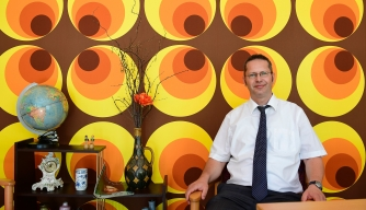"Director of nursing home Gunter Wolfram poses in a 70s styled ""memory room"" in Dresden, Germany. This innovative approach uses decor, meals and music of East Germany of the 1960s and 1970s which is said to help revive old memories and the residents' sense of self. (Credit: Tobias Schwarz/AFP/Getty Images)"