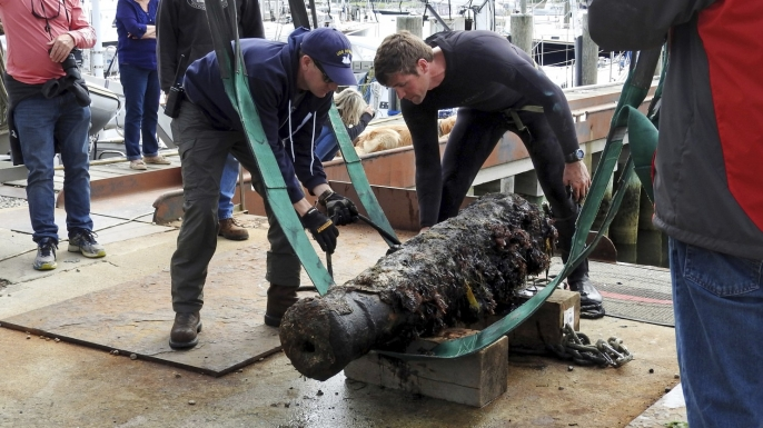 U.S. Navy underwater archaeologist George Schwarz and Explosive Ordnance Disposal Technician Senior Chief Mark Faloon secure a cannon for transportation to the Washington Navy Yard. (U.S. Navy photo by Heather Brown)