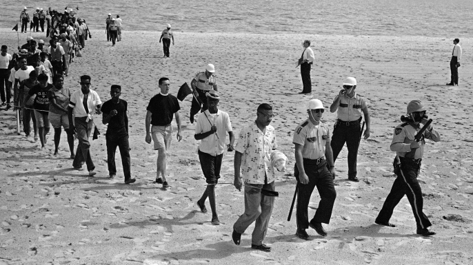 65 black and white demonstrators under arrest troop off the beach at Biloxi after staging unsuccessful attempt to desegregate the Gulf Coast beach. Group was led by Dr. Gilbert Mason (center, foreground) and white minister, Rev. R.G. Gallagher, Biloxi (third in line with shorts). The group was arrested for 'trespassing on private property'. (Credit: AP Photo/Jim Bourdier)