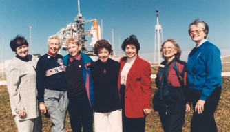 """Members of the First Lady Astronaut Trainees (FLATs), also known as the """"Mercury 13"""" (from left) Gene Nora Jessen, Wally Funk, Jerrie Cobb, Jerri Truhill, Sarah Rutley, Myrtle Cagle and Bernice Steadman. These seven women who once aspired to fly into space stand outside Launch Pad 39B near the Space Shuttle Discovery in this photograph from 1995. (Credit: NASA)"""
