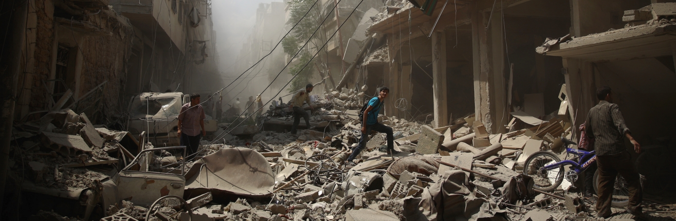 Syrians walk amid the rubble of destroyed buildings following reported air strikes by regime forces in the rebel-held area of Douma, east of the capital Damascus. More than 240,000 people have been killed since Syria's conflict began in March 2011, and half of the country's population has been displaced by the war. (Credit: ABD Doumany/AFP/Getty Images)