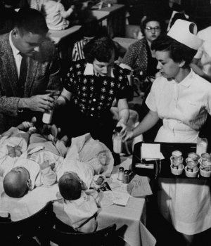 Nurse assisting mother and father during the Queen for a Day program.  (Credit: Ralph Crane/The LIFE Picture Collection/Getty Images)
