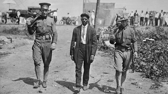 Two National Guard soldiers escort a black man in the aftermath of the East St. Louis Riots.