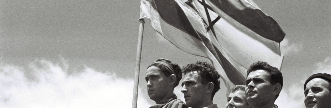 Jewish survivors of the Buchenwald Nazi concentration camp, some still in their camp clothing, stand proudly on the deck of the refugee immigration ship Mataroa July 15, 1945 at Haifa port, during the British Mandate of Palestine, in what would later become the State of Israel. (Credit: Zoltan Kluger/GPO via Getty Images)