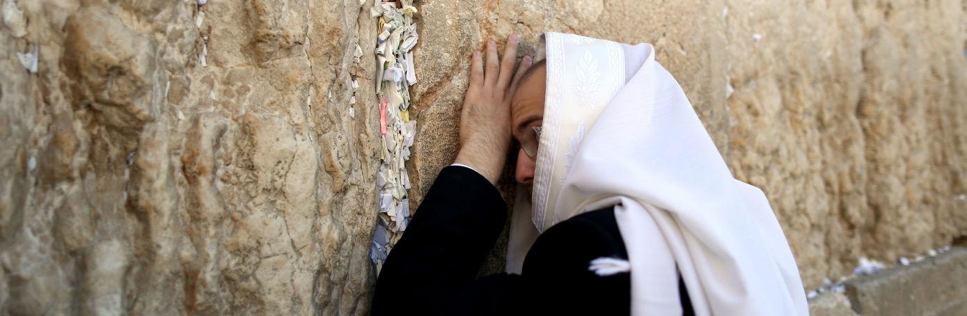 An Orthodox Jew prays next to handwritten notes placed between the ancient stones of the Western Wall, Judaism's holiest site in the Old City of Jerusalem. (Credit: Abir Sultan/Epa/REX/Shutterstock)