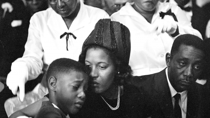 Mrs. Medgar Evers comforts her 9-year-old son, Darrel, at the funeral for integration leader and first Mississippi field secretary of the NAACP Medgar Evers. He was 37 when he was assassinated outside the family's Jackson home. (Credit: AP Photo)