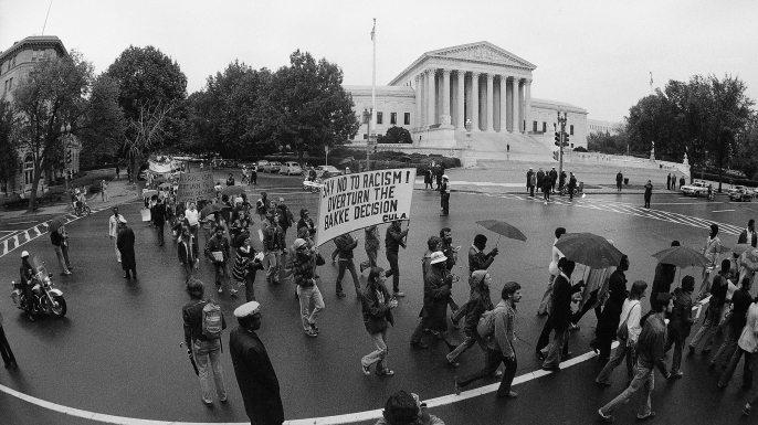 "Demonstrators opposing the Allan Bakke ""reverse discrimination"" case pass the Supreme Court in Washington,1977. (Credit: Charles Tasnadi/AP Photo)"