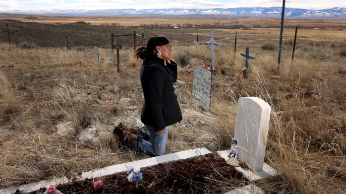 Yufna Soldier Wolf wipes away tears while kneeling at the grave of her great-grandfather, Chief Sharp Nose of the Northern Arapaho Tribe, at the family cemetery on the Wind River Reservation near Riverton, Wyo. Soldier Wolf is seeking the remains of her great-uncle Little Chief, who died while attending Carlisle Indian School in Carlisle, Pennsylvania. (Credit: Dan Cepeda/The Casper Star-Tribune/AP Photo)