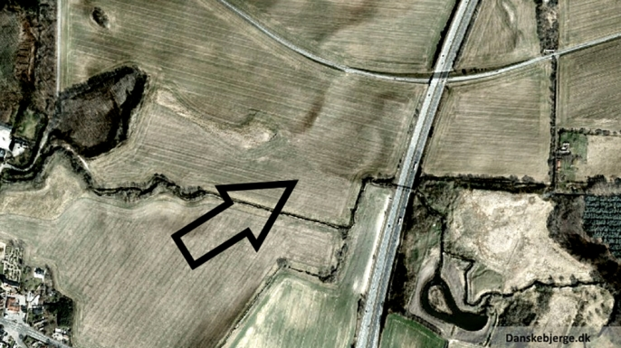 Satellite photo with added hill shade, revealing the circular formation discovered, pointed out by the arrow. (Credit: Danskebjerge/Wikimedia Commons/CC BY-SA 3.0)