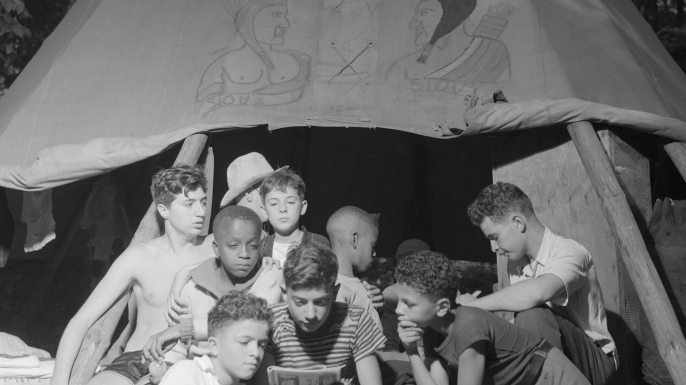 Boys sharing a comic book at the racially integrated Camp Nathan Hale in Southfields, NY, 1943. (Credit: Gordon Parks/Everett Collection Inc/Alamy Stock Photo)