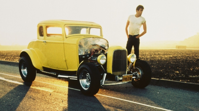 Actor Paul Le Mat, standing beside a Ford Model B five-window coupe, also known as the Deuce Coupe, in a publicity still for the film American Graffiti. (Credit: Silver Screen Collection/Getty Images)