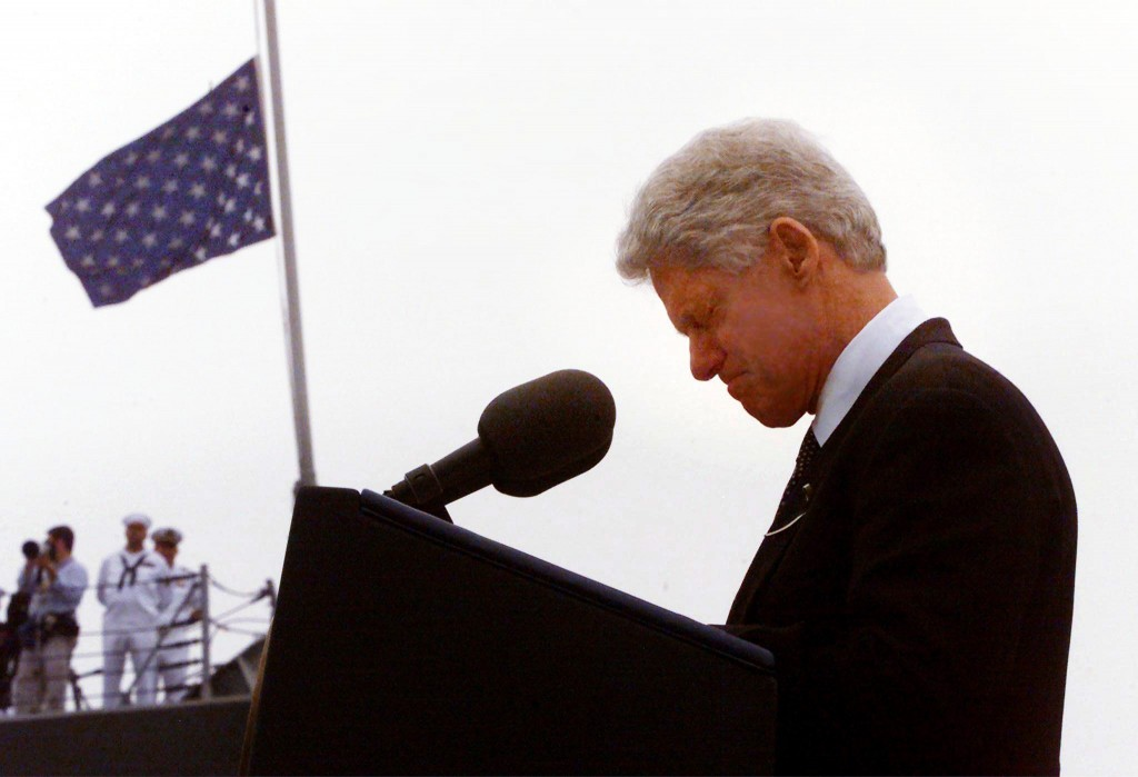 President Bill Clinton bows his head in a moment of silence during a memorial service for victims of the explosion on the USS Cole, 18 October, 2000. The attack in Yemen left 17 US sailors dead and 39 injured. (Credit: Mario Tama/AFP/Getty Images)