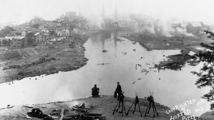 Soldiers sit on a hill overlooking Johnstown, Pennsylvania after the 1889 flood. (Credit: Histed/Library of Congress/Corbis/VCG via Getty Images)
